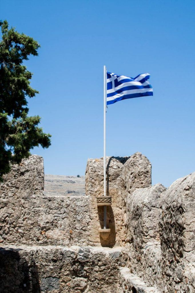 Lindos is for TouristsThe Greek flag waving in the breeze at the castle ruins of Lindos.
