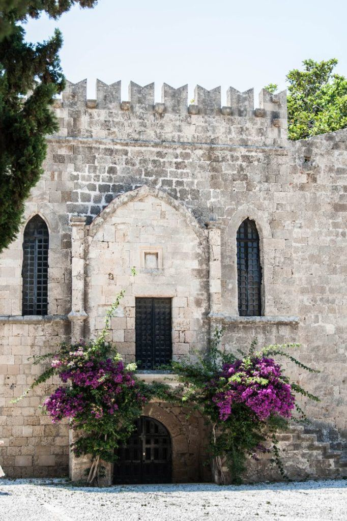 Purple flowering bushes adorn the Medieval dungeon entrance in Rhodes.
