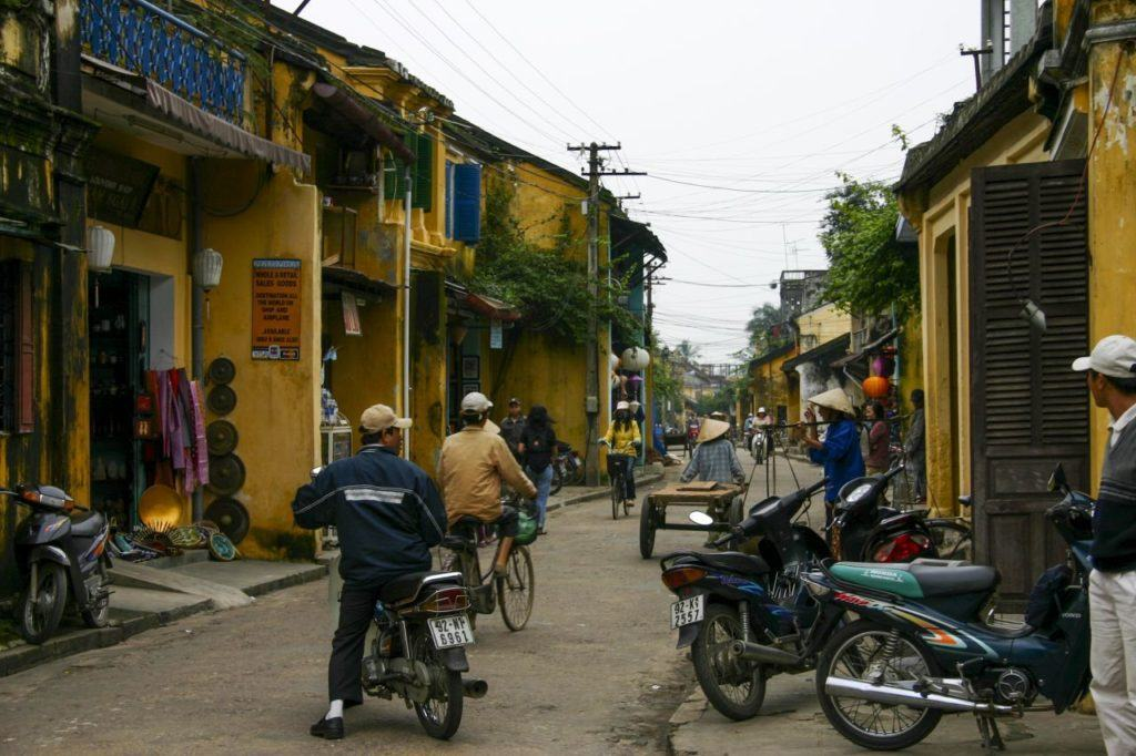 Street traffic in a backroad of Hoi An with colorful yellow buildings.