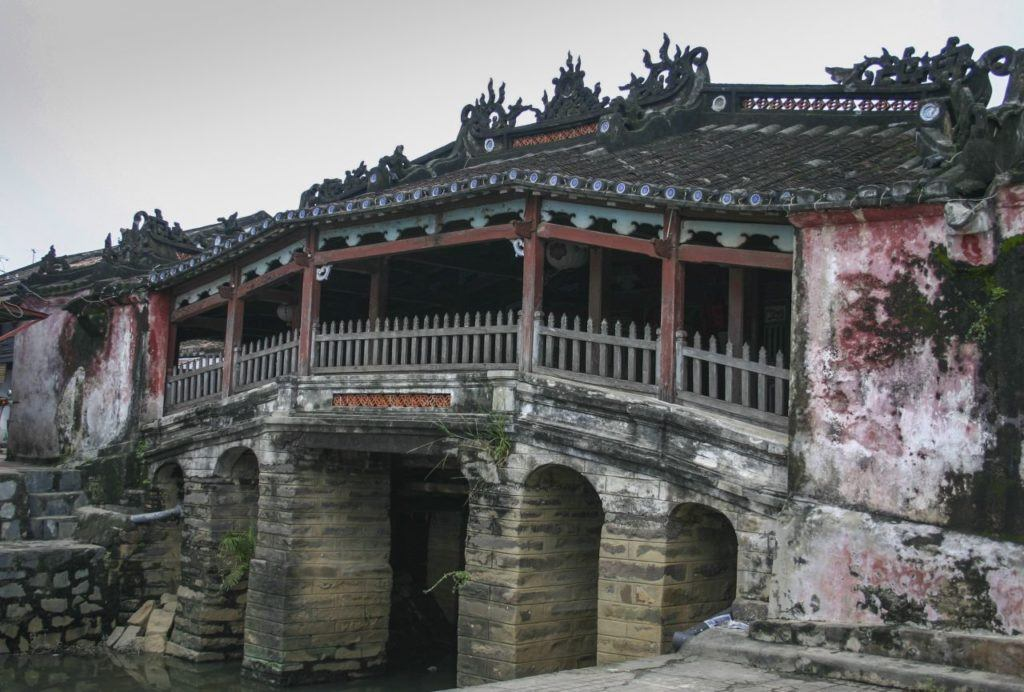 Covered bridge with ornate dragon sculptures.