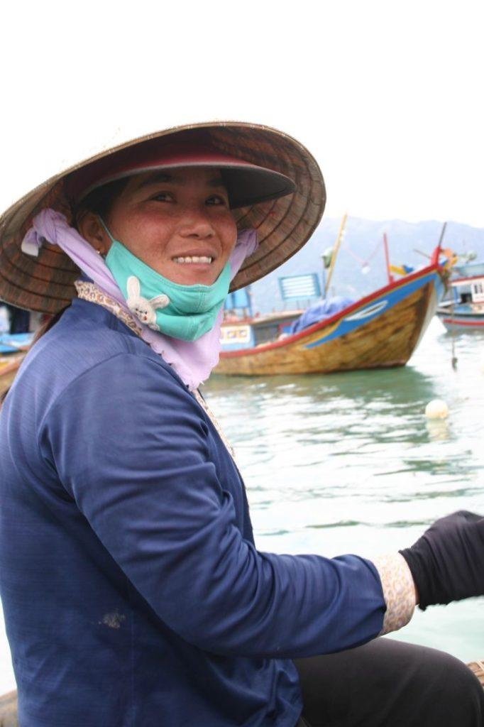 Vietnamese woman rows our small basket boat.