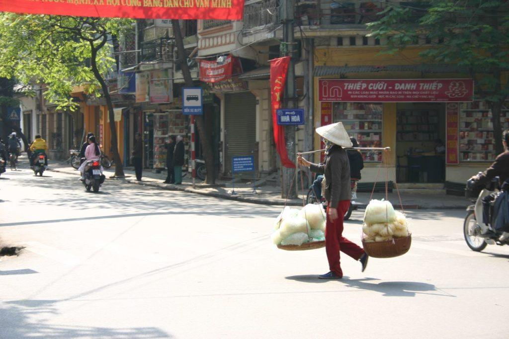 Woman crosses the road carrying a load balanced on baskets.