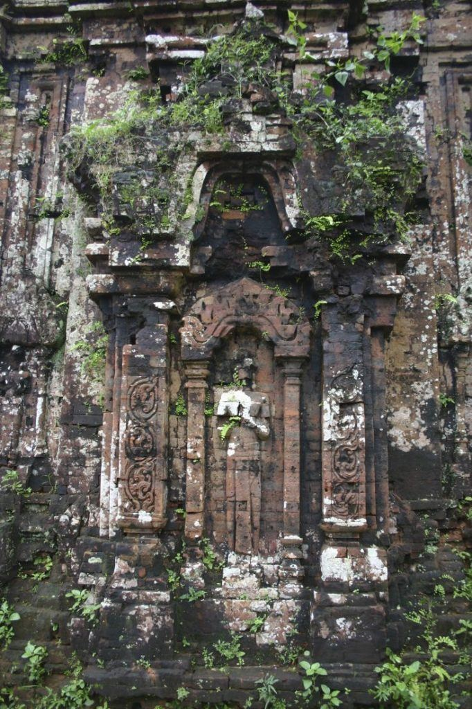 Overgrown relief carving on a temple wall in Hue.
