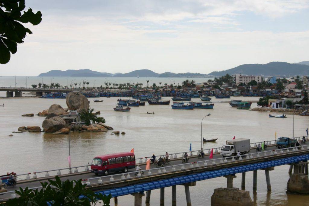 Visiting Small island shrine in Nha Trang Bay with road traffic crossing a bridge and fishing boats moored behind.