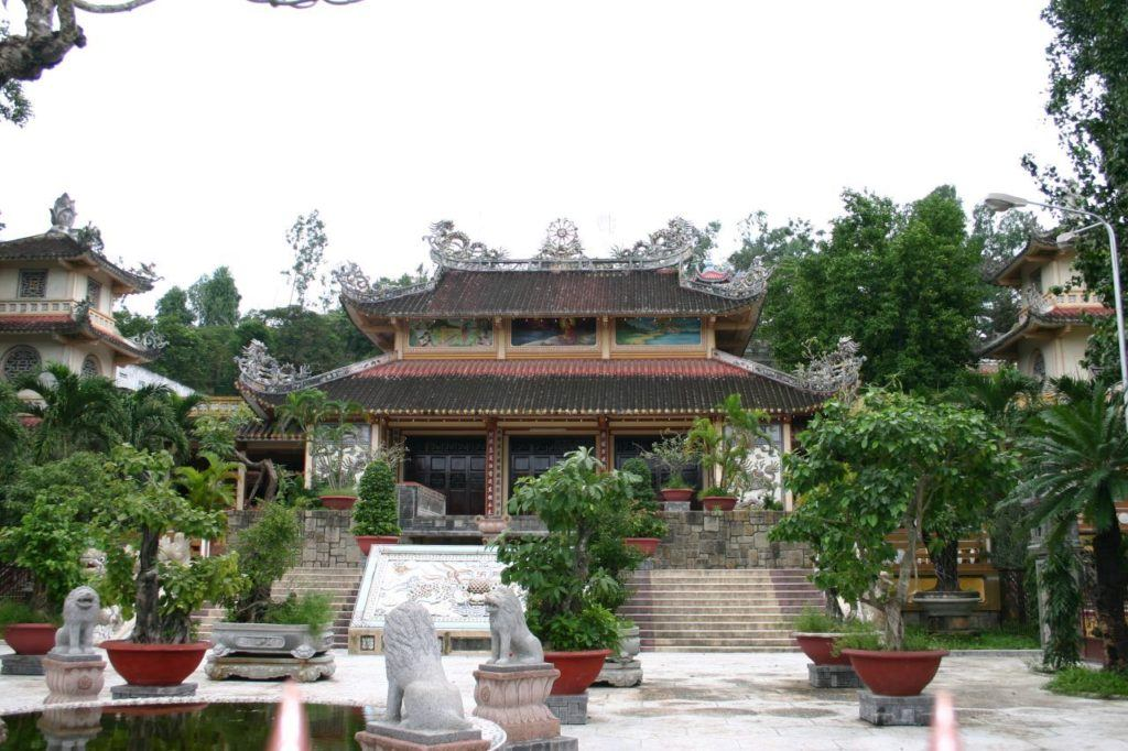 Vietnamese temple garden with pond, lion statues, and colorfully painted walls.