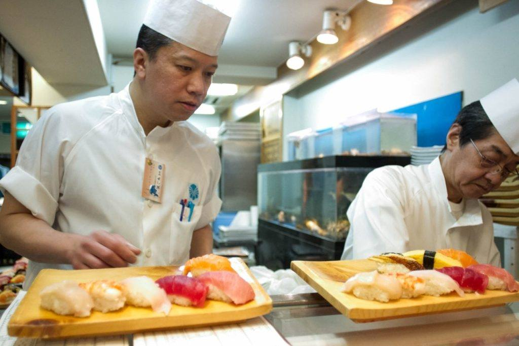 Two sushi chefs present breakfast at the Tsukiji Market.