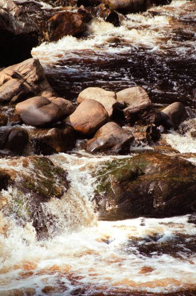 Rocky river with rusty colored water.