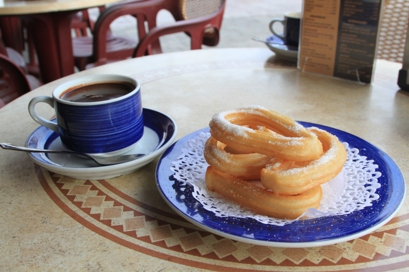 Churros y Chocolate in an outdoor cafe in Llanes.