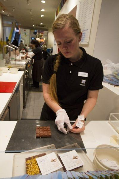 A women packaging chooclate bars at the make your won chocolate bar store.