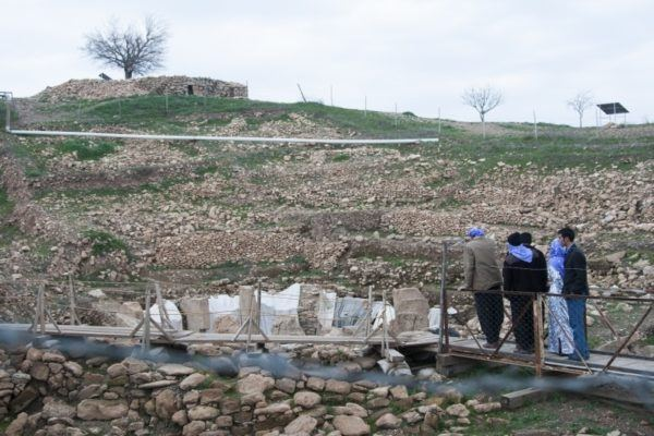 A small group stands on the platform overlooking Gobekli Tepe.