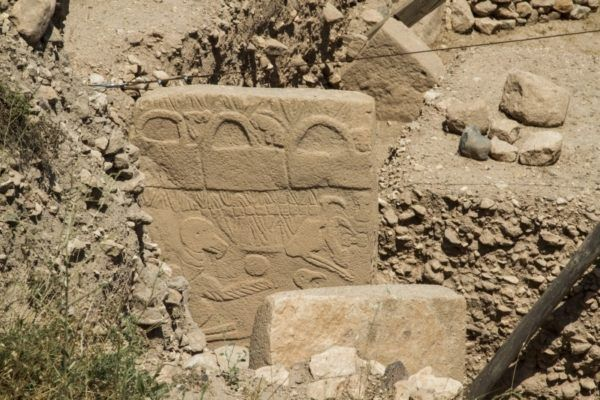 Large standing stone carved with strange animal reliefs.