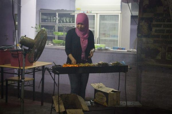 Frilling up some tasty meat sticks at one of Brunei's hawker stalls.