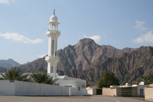 A white mosque in front of a mountain in UAE.