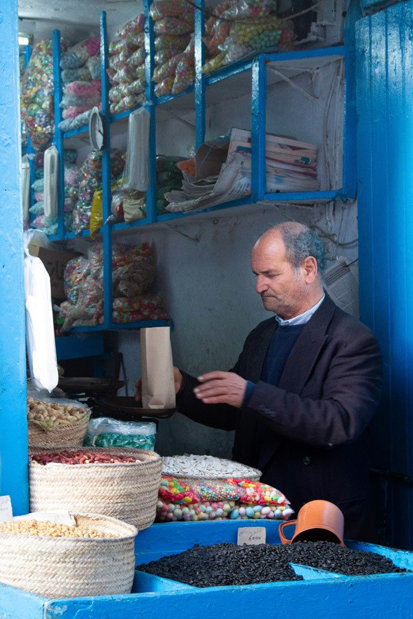 A vendor selling snacks and nuts in the Tunis souk.
