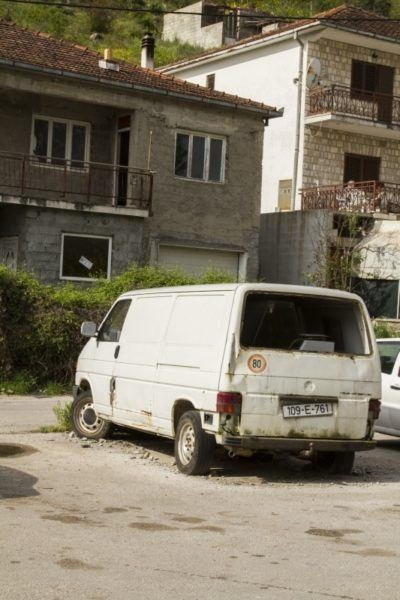 Old van surrounded by rubble in Bosnia.