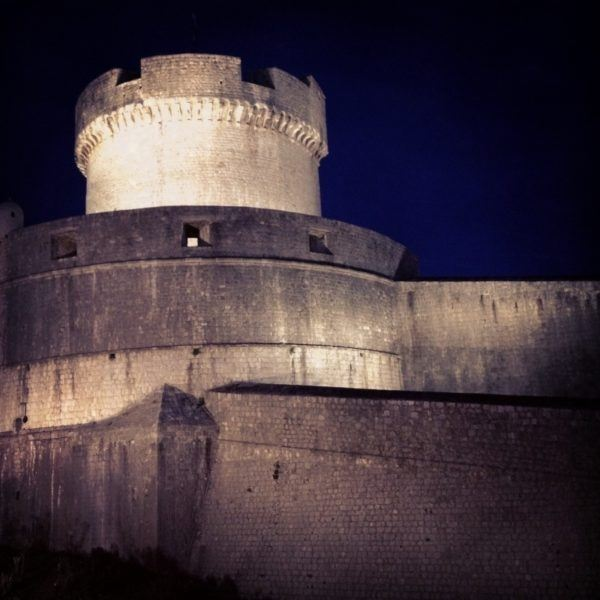 Dubrovnik city wall and defensive tower at night.