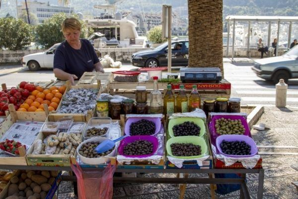 Market scene with woman selling olives and dried fruits.