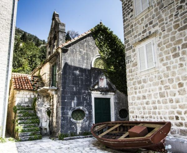 Old fishing boat near ancient stone buildings in Perast.