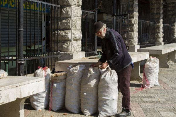 Old man in packing up his wares at the Kotor market.