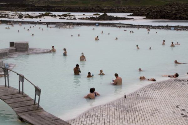 Bathers with mud on their faces and others just relaxing in the Blue Lagoon.