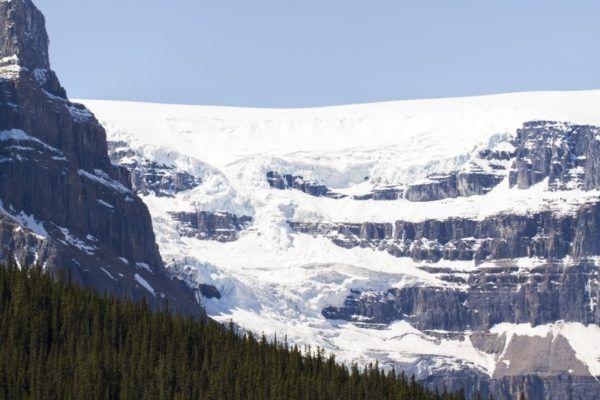 Massive glacier hangs over the edge of a cliff.