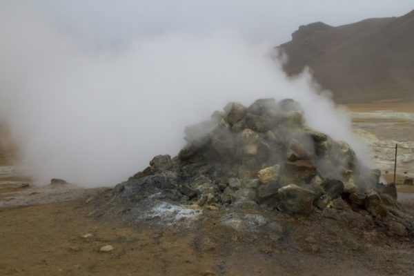 A standard example of a fumerole releasing hot steam and gases from deep within the earth.