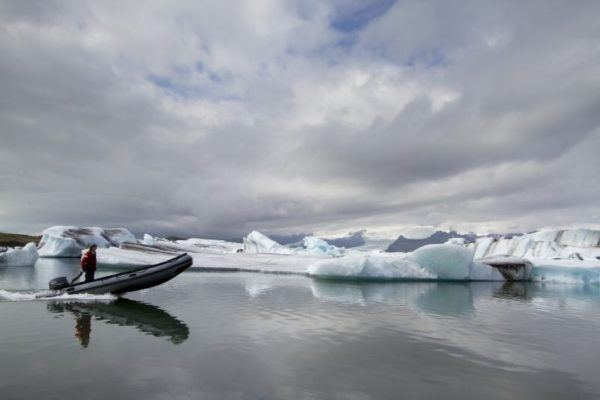 Lone boater skims across the water in front of icebergs in the lagoon.