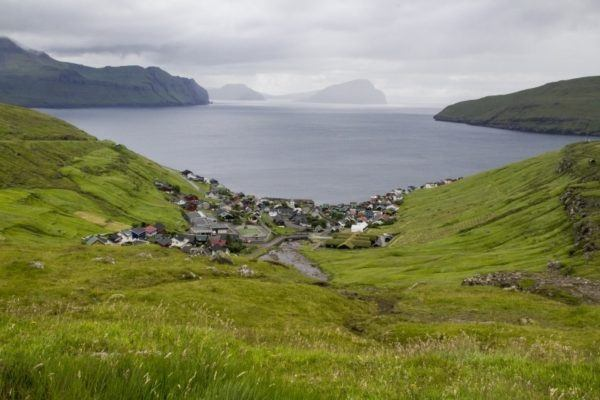 Looking down a grassy slope to a fishing villages nestled in a bay on the Faroe Islands.