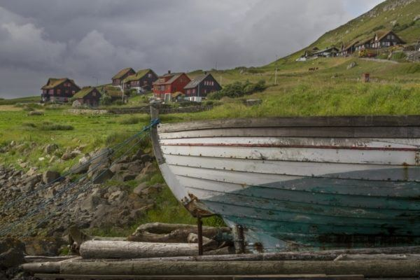 Old wooden fishing boat perched on the shore.