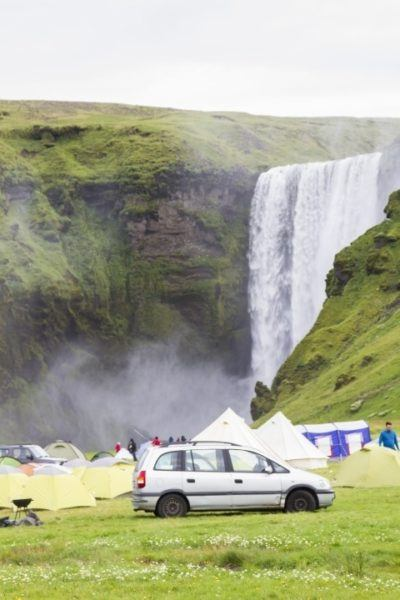 A small free campground near an Icelandic waterfall.