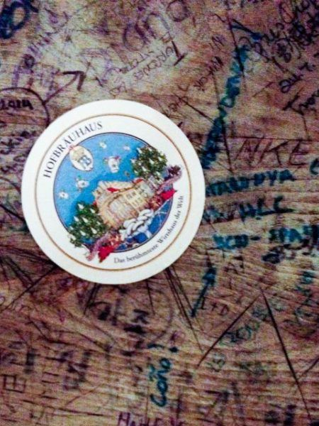 Hofbrauhaus table with grafitti and a coaster.