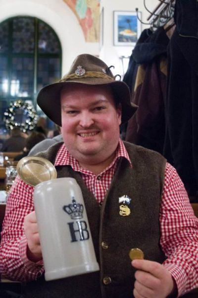 A long time Hofbrauhaus fan, the man shows off his coin and stein.