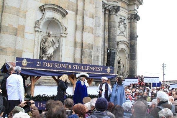The MC tells the history of the giant Dresden stollen and welcomes everyone to have a piece at the end of the parade route.