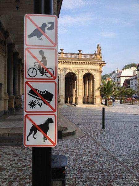 Karlovy Vary pedestrian zone advisory sign - no feeding the pigeons, no biking, stay off the flowers, no dogs.
