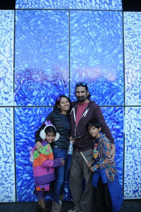 Family in front of blue wall.
