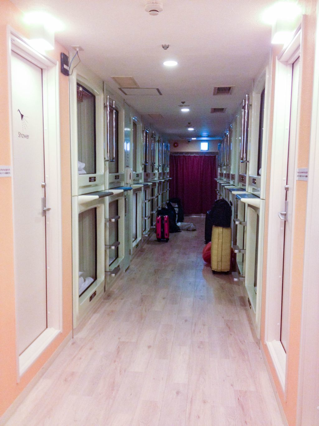Double decker sleeping pods line the hallway for this capsule hotel