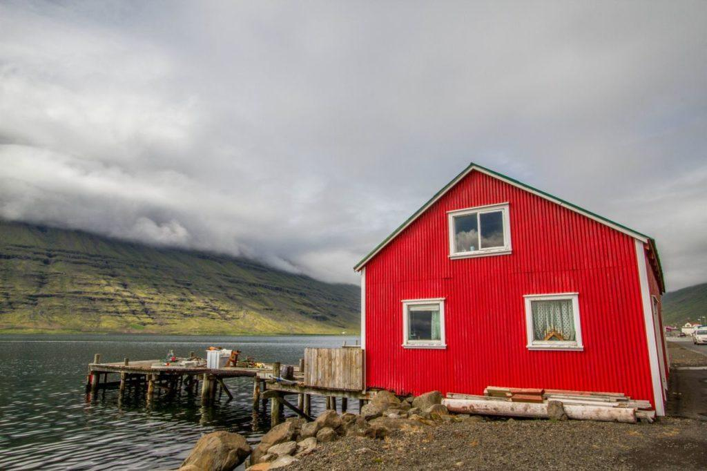 Traditional red with white trim boat house on an Icelandic fjord.