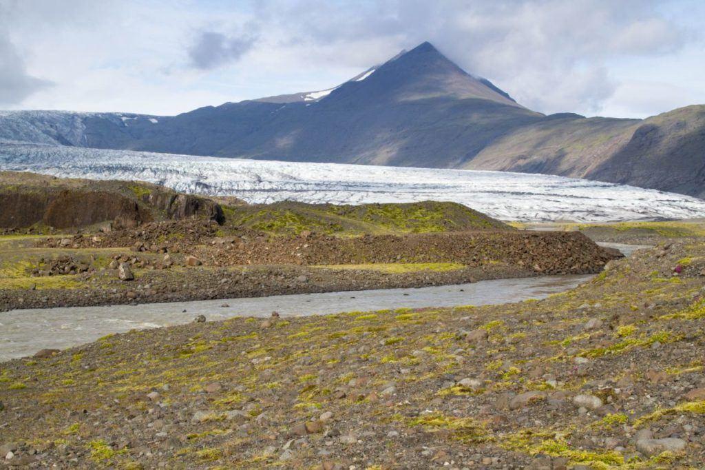Massive roadside glacier with a small runoff river.