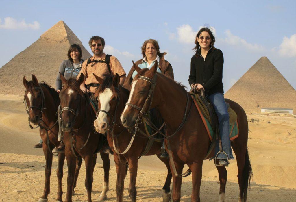 Family Riding Horses at the pyramids in Giza.