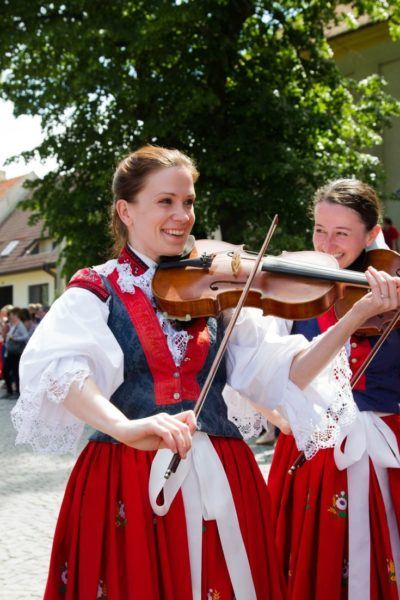 Two women in traditional Czech dress play the violin for folk dancers at Ride of the Kings in Vlčnov.