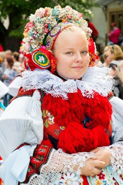 Smiling Czech girl wearing traditional head dress with flowers, beads, and embroidery.