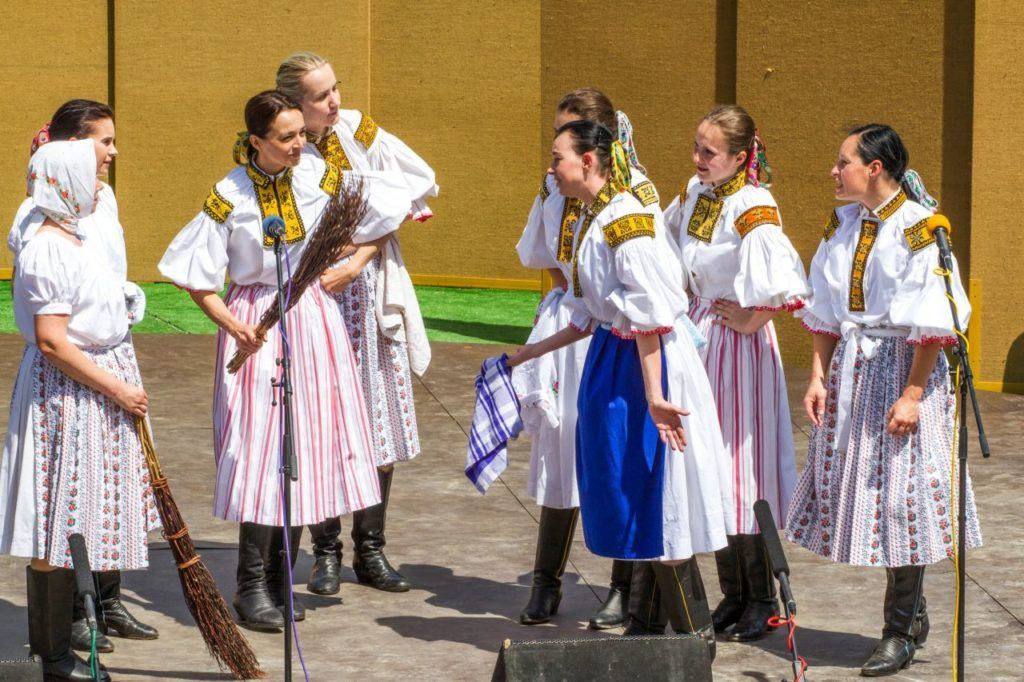 Young Czech women in folk costume perform on stage during the Ride of the King festival.