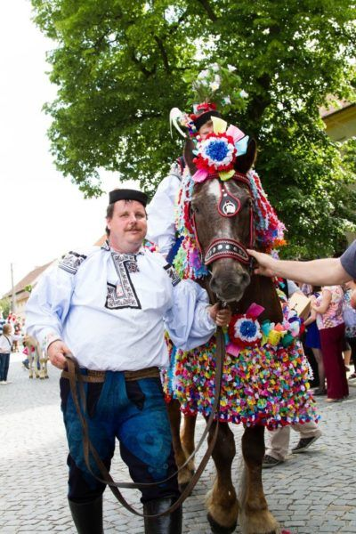 The young camouflaged king sits high atop a colorfully decorated horst at the Ride of the Kings in Czechia.