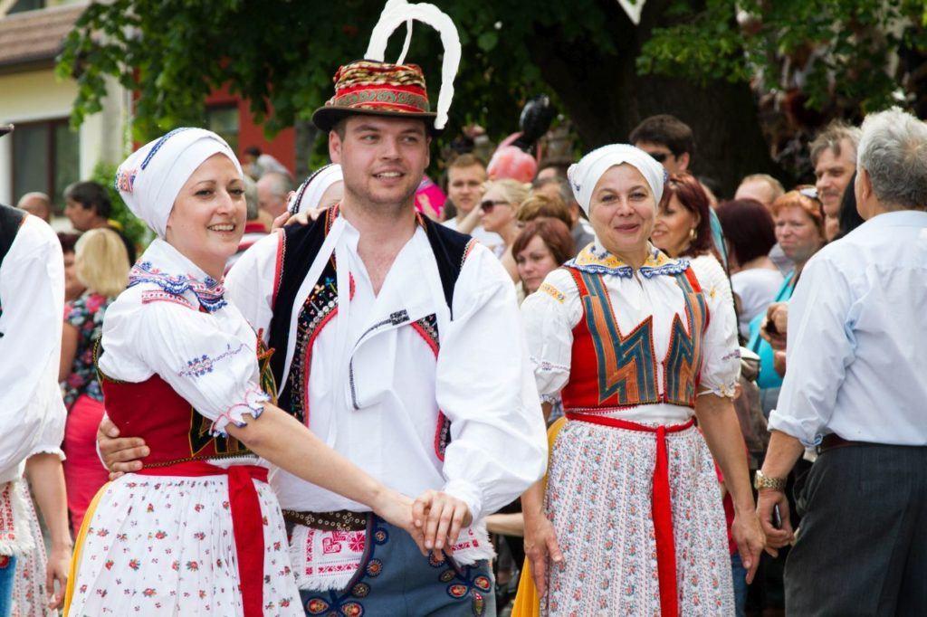 Young couple in trtaditioanl Czech attire begin a folk dance.