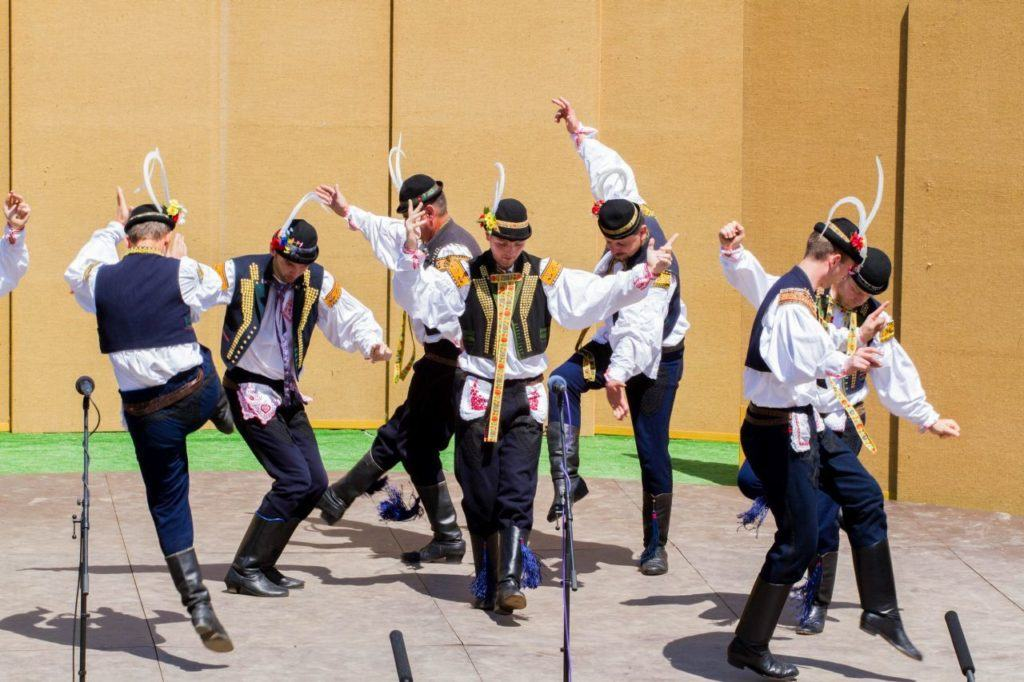 Young men in traditional Czech outfits and leather boots perform a folk dance.