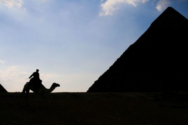 Silhouette of soldier and pyramid.