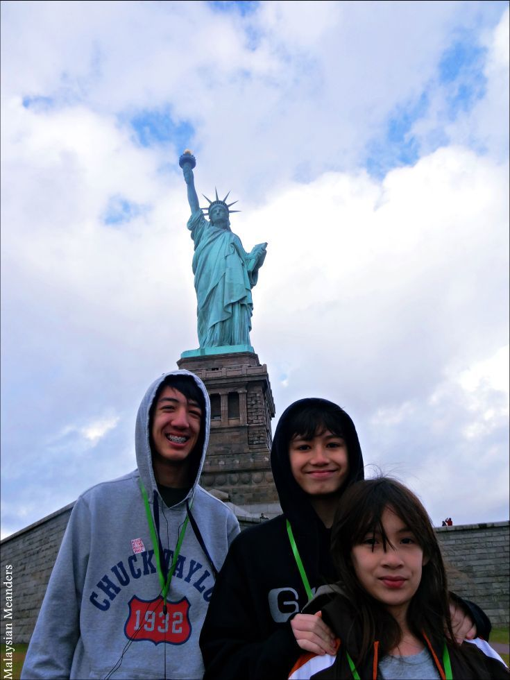 The family in front of the Statue of Liberty.