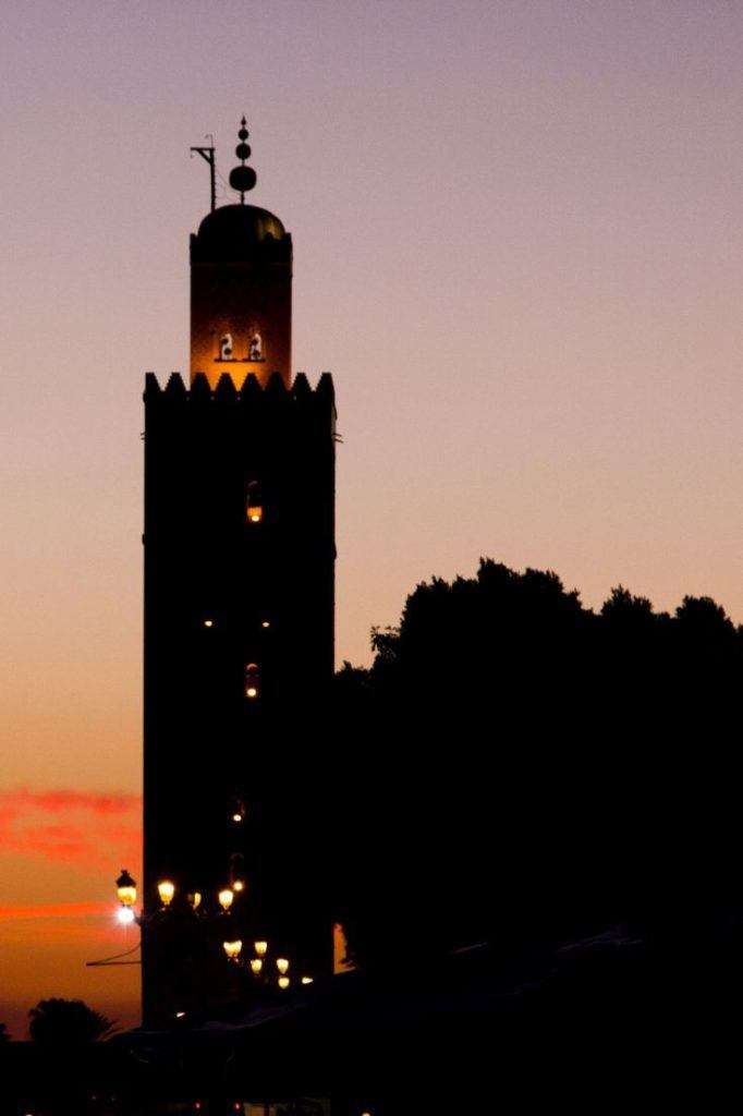Marrakesh with a silhouetted mosque tower at sunset.