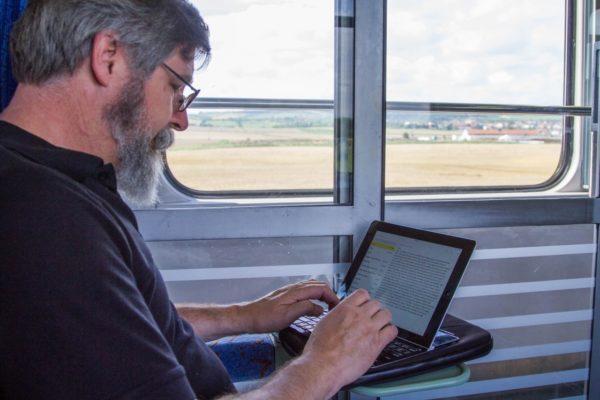 Jim working on his ipad while enjoying train travel in Eastern Europe.