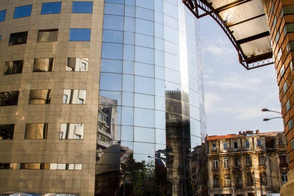 Bucharest street scene reflected in a modern building.
